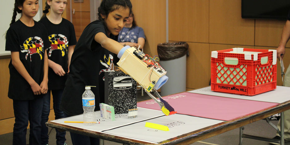 Girls competing in MESA competition with mechanical arm