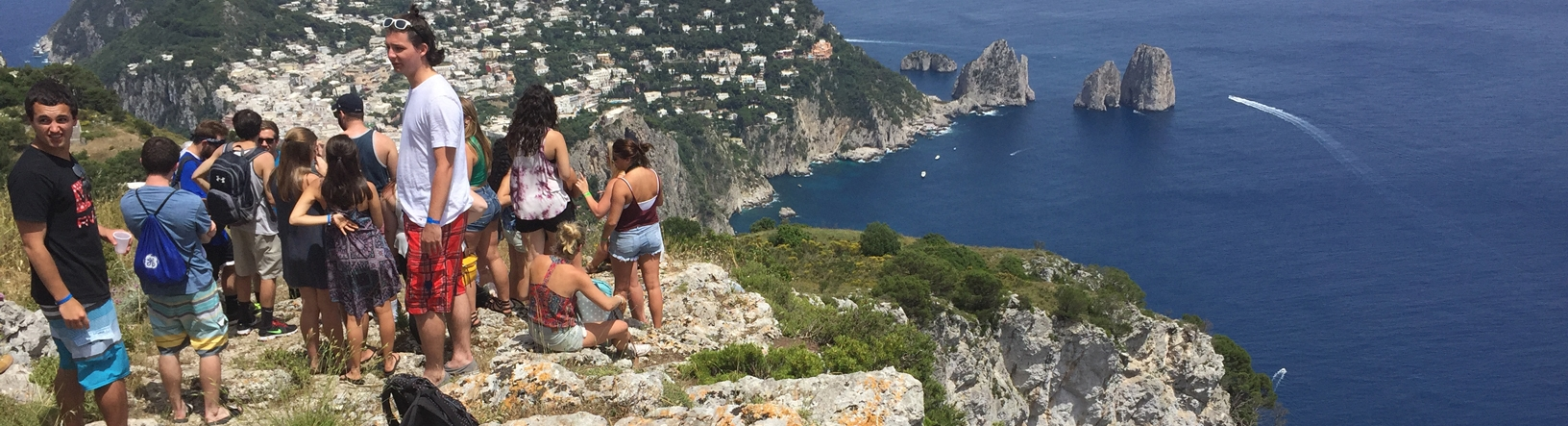 Study abroad students standing cliff side over looking the ocean with Temple flag
