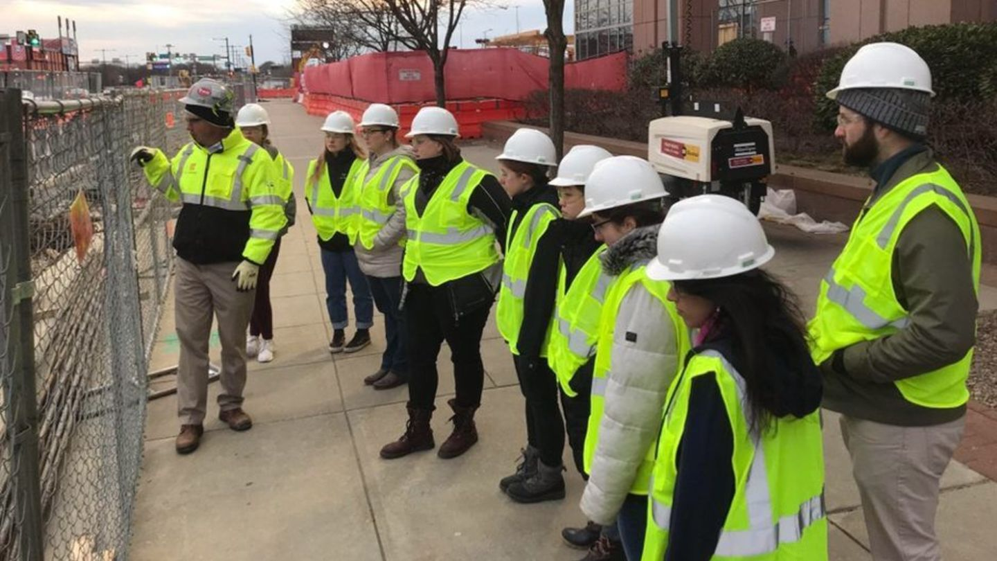 students in hard hats at construction site