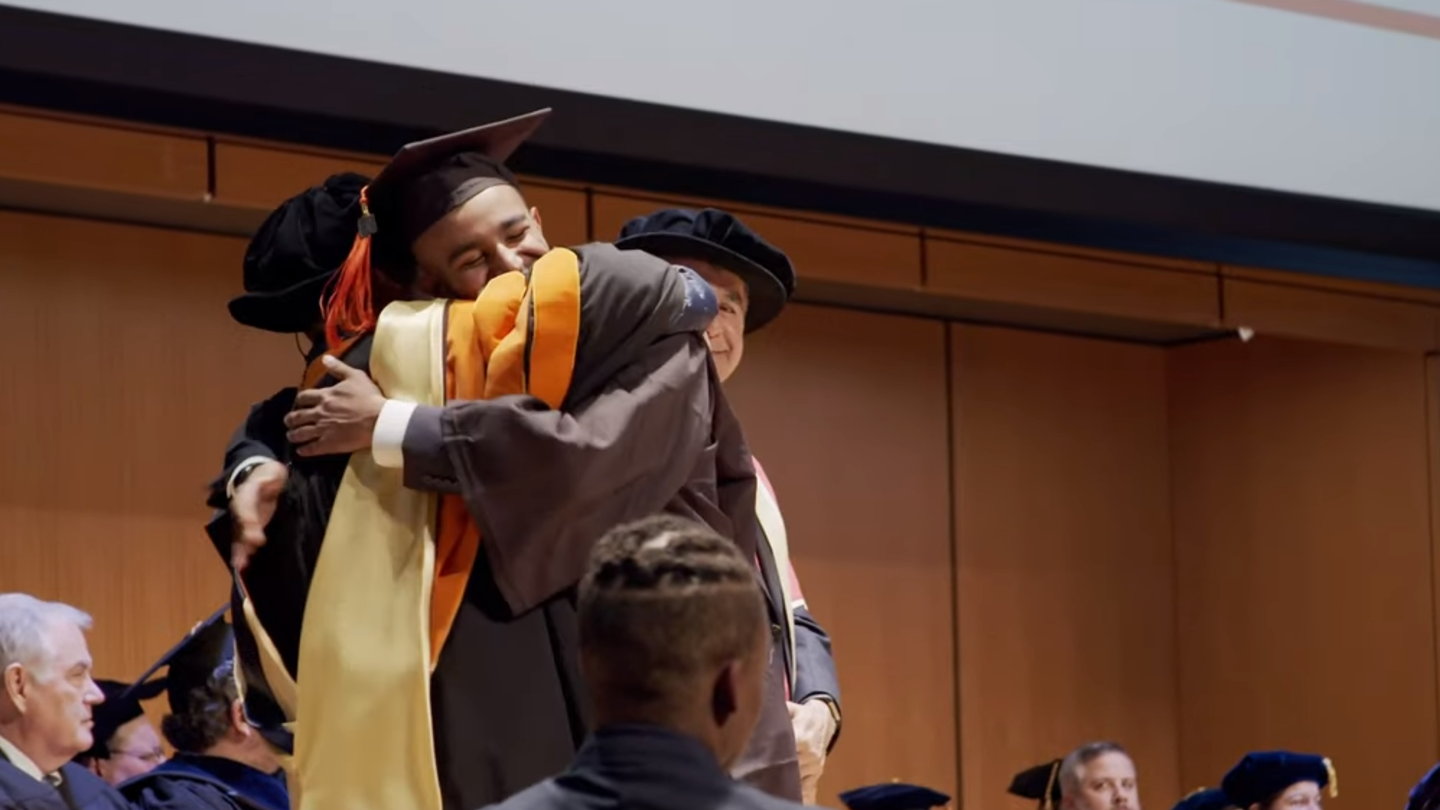 student embracing faculty member